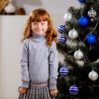 Girl smiling near Christmas tree — Stock Photo