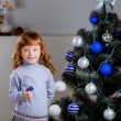 Girl with a gift near the Christmas tree — Stockfoto