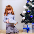 Little girl with gifts under the Christmas tree — Stock Photo