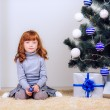 Little girl with gifts under the Christmas tree — Stock Photo #32285473