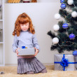 Little girl opens a gift — Stock Photo #32285475