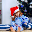 Child in pajamas near the Christmas tree — ストック写真