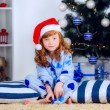 Child in pajamas near the Christmas tree — Stock Photo #32285531