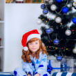 Child in pajamas near the Christmas tree — Stockfoto