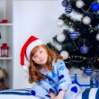 Child in pajamas near the Christmas tree — Stock Photo #32285535