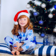 Child in pajamas near the Christmas tree — Stock fotografie