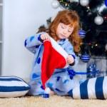 Child in pajamas near the Christmas tree — Stock Photo #32285549