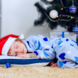 Child fell asleep near the Christmas tree — Stock Photo
