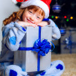Little girl in Christmas hat with a New Year gift — Stock fotografie