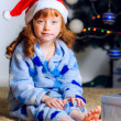 Child with a gift near the Christmas tree — Foto de Stock