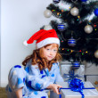 Little girl opens gift under  the Christmas tree — Stock Photo