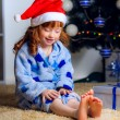 Child with a gift near the Christmas tree — Stock Photo