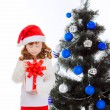 Red-haired girl opening a gift near the Christmas tree — Stock Photo #32285613