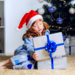Little girl opens gift under  the Christmas tree — Foto Stock