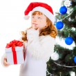 Dreaming girl in a Christmas hat with gifts — Stock Photo #32285651