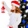 Red-haired  girl in a Christmas hat with flashlight. — Stock Photo