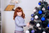 девушка висит на новогодние игрушки — Стоковое фото