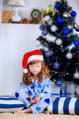 Child in pajamas near the Christmas tree — Stock Photo