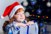 Little girl in Christmas hat with a New Year gift — Stock Photo