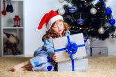 Little girl opens gift under the Christmas tree — Stock Photo