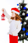 Red-haired girl in a Christmas hat with flashlight. — Foto de Stock