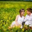 Young family sitting down on dry grass in summer field — Stockfoto