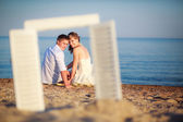 Newlyweds looking through the window frame — Stock Photo