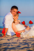 Weeding couple on the sand with watermelon decorations — Stock Photo