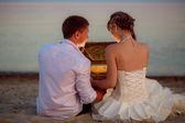 Wedding couple on the beach open casket — Stock Photo
