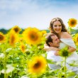Groom holds his bride  among the sunflowers — Stock Photo