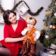 Mother and son near Christmas tree — Stock Photo #33596177
