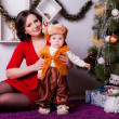 Mother and son near Christmas tree — Stock Photo #33596187