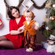 Mother and son near Christmas tree — Stock Photo #33596195
