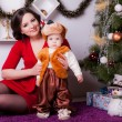 Mother and son near Christmas tree — Stock Photo #33596205