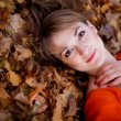 Beautiful girl lying on autumn leaves.  — Stockfoto