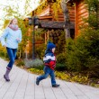 Sister and younger brother  running in park — Stock Photo
