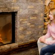 Girl sitting  near the fireplace — Stock Photo