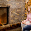 Stock Photo: Girl sitting near fireplace