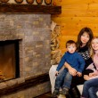 Mom with her daughter and son sitting  near the fireplace — Stock Photo