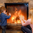Stock Photo: Brother and sister heated hands near fireplace
