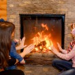 Stock Photo: Mom with her daughter and son heated hands near fireplace