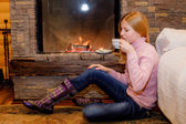 Girl is drinking tea near fireplace — Stock Photo