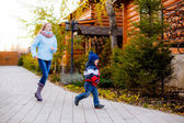 Sister and younger brother running in park — Foto Stock