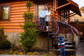 Mother with her daughter and son near a wooden house — Stock Photo