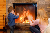Brother and sister heated hands near the fireplace — Stock Photo