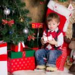pojke med gåvor nära en julgran — Stockfoto