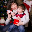 Mother and son opening christmas gifts — Stock Photo #34350263
