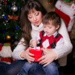 Mother and son opening christmas gifts — Stock Photo #34350267