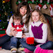 Family near the Christmas tree opening gifts. — Stockfoto