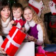 Family near the Christmas tree opening gifts. — Stok fotoğraf